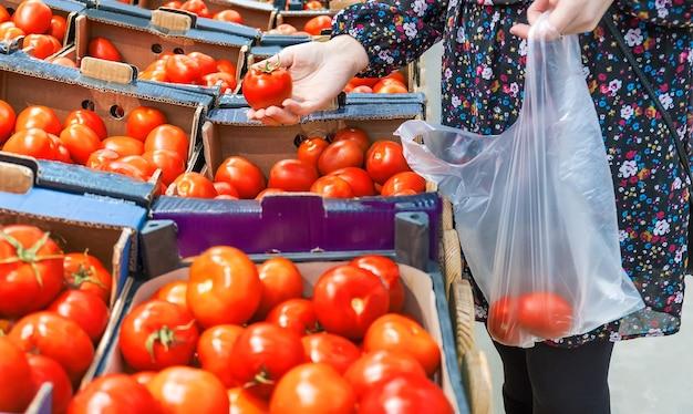 Een vrouw kiest tomaten in een supermarkt. selectieve aandacht. eten.