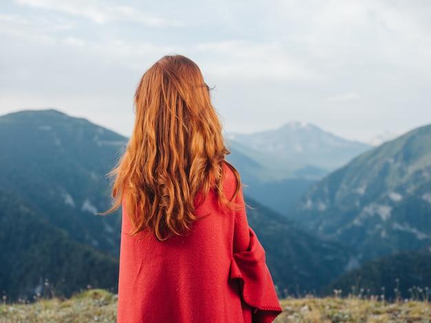 Een vrouw kijkt naar de bergen in de natuur en een rode plaid op haar schouders. hoge kwaliteit foto