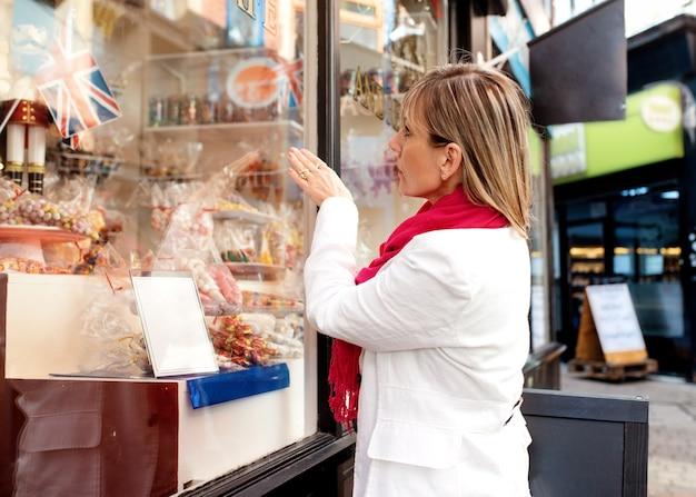 Een vrouw kijkt naar snoep in het raam van een café