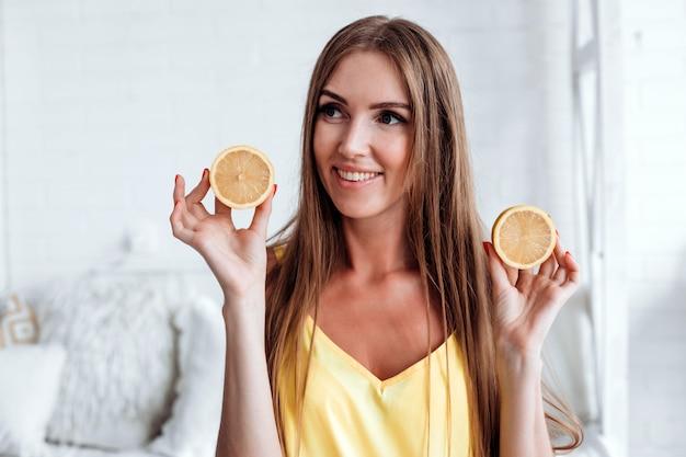 Een vrouw kijkt weg terwijl ze een gesneden citroen vasthoudt