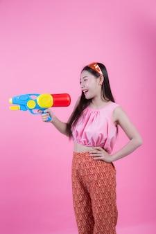 Een vrouw kleedde zich in traditionele thaise volkskleren houdend een waterkanon op een roze achtergrond.