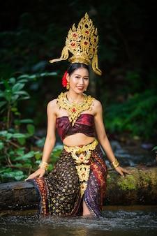 Een vrouw kleedde zich met een oude thaise jurk aan de waterval.