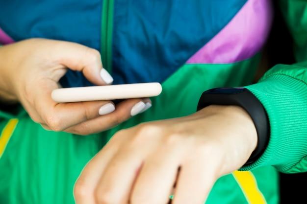Een vrouw klikt op haar smartphone om de fitnessarmband aan te passen. in een sport heldergroene jas voor sport. gezond leefstijl- en fitnessconcept