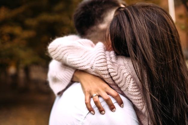 Een vrouw knuffelt haar geliefde man heel stevig in het park in de herfst bos herfst liefdesrelatie