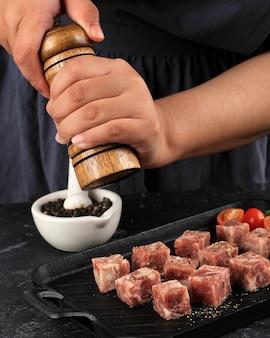 Een vrouw kookt met paprika's verse rauwe saikoro blokjes gesneden steaks van gemarmerd japans rundvlees op een donkere achtergrond.