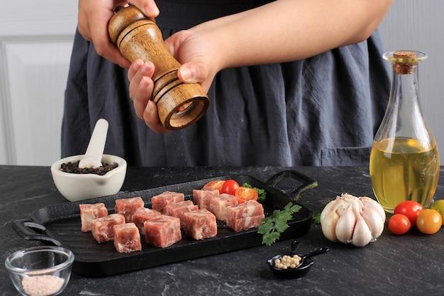 Een vrouw kookt met zout en zwarte peper verse rauwe saikoro blokjes gesneden steaks van gemarmerd japans rundvlees op een witte keuken achtergrond.