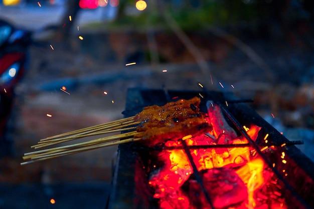 Een vrouw kookt saté kebabs, populair in maleisië en indonesië, op straat. straatvoedsel in maleisië.