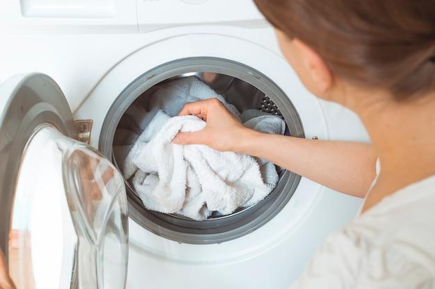 Een vrouw laadt vuile kleren voor een wasmachine.