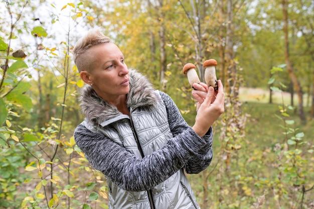 Een vrouw laat de paddenstoelen zien die in het bos zijn gevonden. voor elk doel.