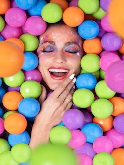 Een vrouw lachend, met haar ogen dicht, ondergedompeld in gekleurde ballen. vreugde concept. selectieve aandacht.