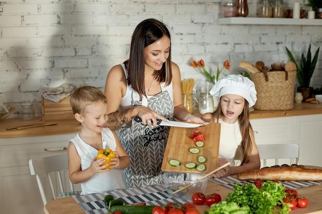 Een vrouw leert haar dochter koken van haar zoon