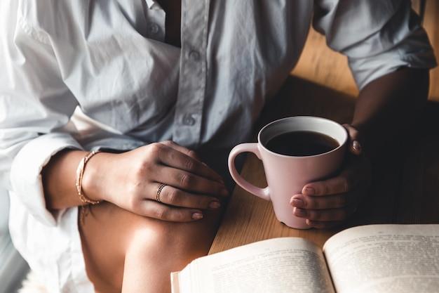 Een vrouw leest een boek. onderwijs, opleiding, leren, hobby. manicure Premium Foto