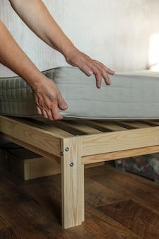Een vrouw legt een matras op het bed of stelt het reinigingsproces uit