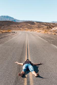 Een vrouw ligt blootsvoets op een lege weg in de death valley