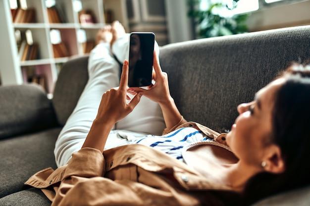 Een vrouw ligt op de bank met een telefoon in de woonkamer. communicatie, online winkelen. een vrouw met een smartphone communiceert, rust en heeft plezier. smartphone leeg scherm.