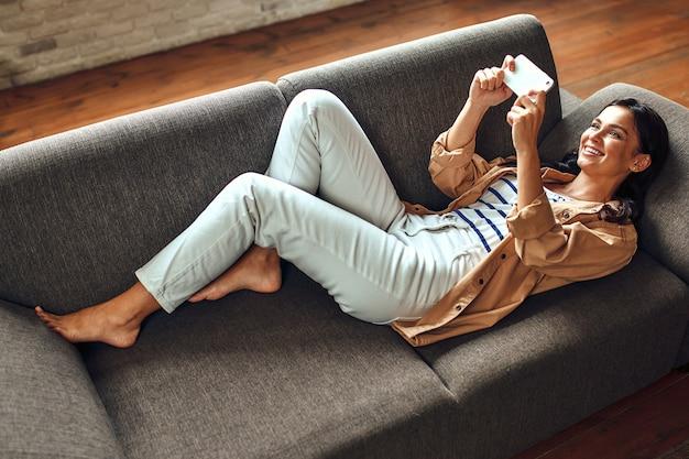 Een vrouw ligt op de bank met een telefoon in de woonkamer. communicatie, online winkelen. een vrouw met een smartphone communiceert, rust en heeft plezier.