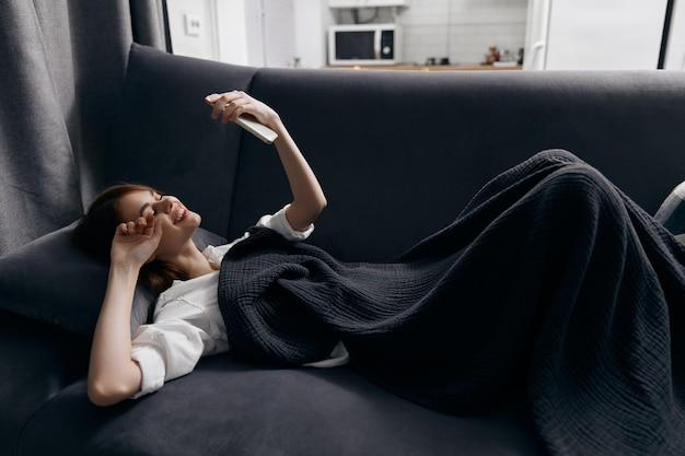 Een vrouw ligt op een bank in een appartement met een mobiele telefoon in haar hand. hoge kwaliteit foto