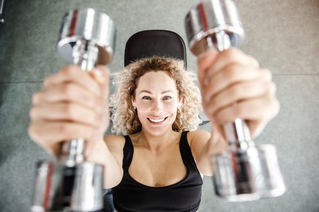 Een vrouw ligt op een trainingsapparaat op een achtergrond