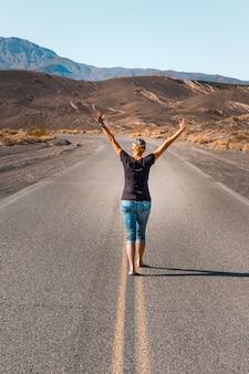 Een vrouw loopt blootsvoets over een lege weg in de death valley