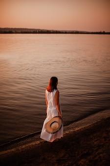 Een vrouw loopt op het strand achteraanzicht van een jonge vrouw in een lange witte jurk en blootsvoets...
