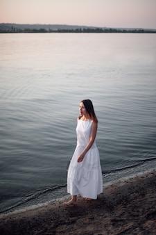 Een vrouw loopt op het strand levensstijl full-length portret van een jonge vrouw in een mooie witte jurk...