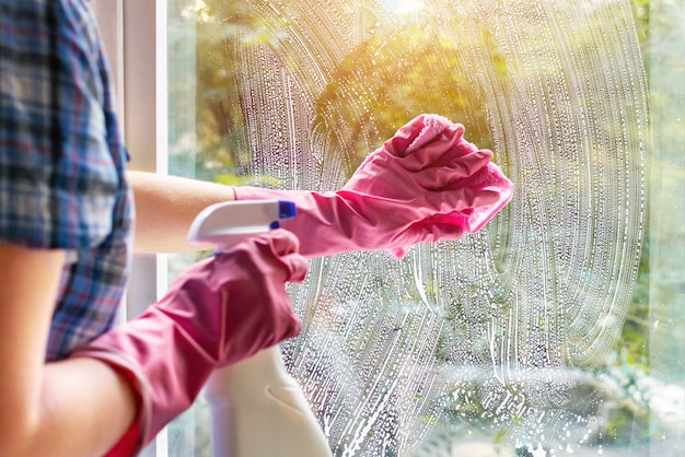 Een vrouw maakt een ruit schoon met een doek en zeepsop. reinigen met een afwasmiddel. handen in roze beschermende handschoenen wassen glas op de ramen van het huis met een spuitfles, huis routine concept.