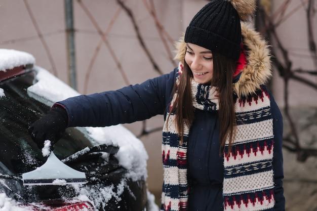 Een vrouw maakt een sneeuwraam op een auto schoon met een sneeuwschraper.