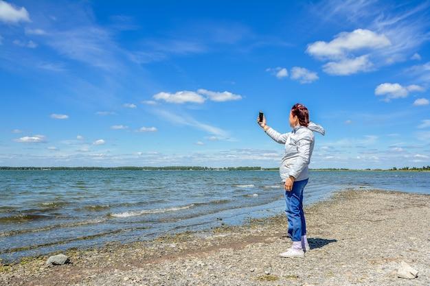 Een vrouw maakt foto's van een prachtig landschap op haar smartphone