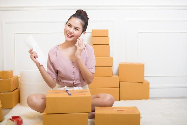 Een vrouw maakt producten met kartonnen dozen klaar voor verzending.
