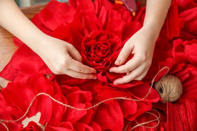 Een vrouw maakt rode papieren bloemen. alleen de wijzers zitten in het frame. bovenaanzicht. hoge kwaliteit foto