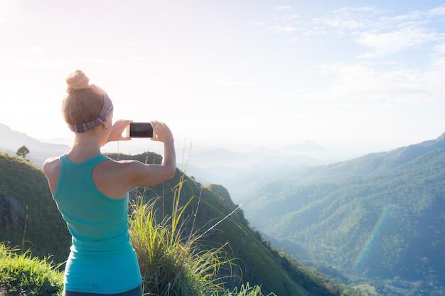 Een vrouw maakt 's ochtends foto's van de bergen vanaf de top van de berg