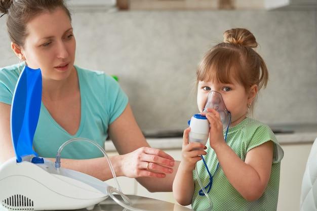 Een vrouw maakt thuis inademing aan een kind. brengt het vernevelaarmasker naar zijn gezicht. inhaleert de damp van het medicijn.