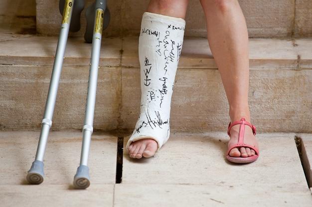 Een vrouw met been in gips en krukken