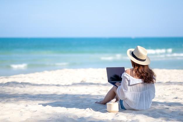 Een vrouw met behulp van en typen op het toetsenbord van de laptop computer zittend op een prachtig strand