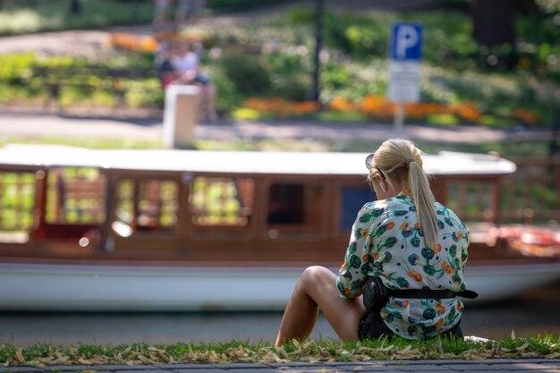 Een vrouw met blond haar zit aan de gracht en kijkt naar het schip