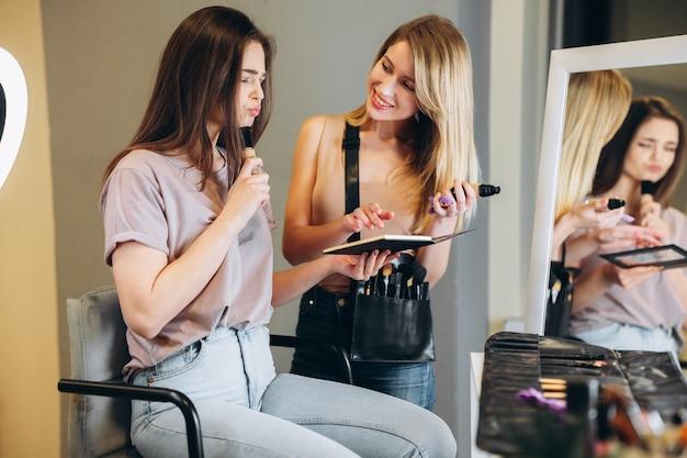 Een vrouw met bruin haar wijst met haar vinger naar de geselecteerde oogschaduwkleur. visagist en klant kiezen de kleur van de oogschaduw.