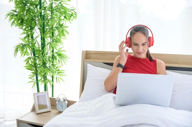 Een vrouw met casual kleding die vanuit huis werkt, online vergadert, videogesprek voert, conferenties houdt, online winkelt en online studeert