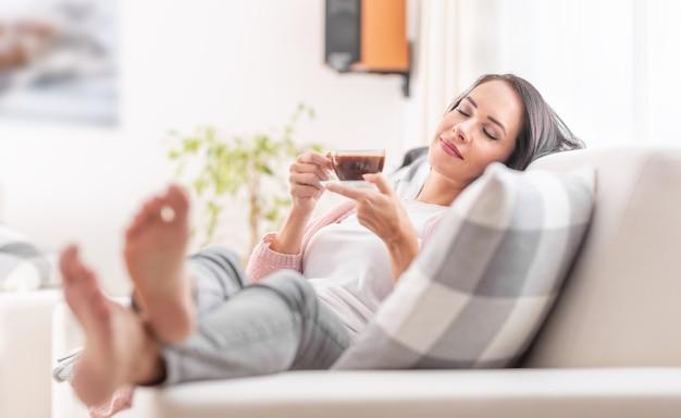 Een vrouw met de voeten omhoog in een comfortabele outfit geniet thuis van een rustige tijd van ontspanning op haar bank.