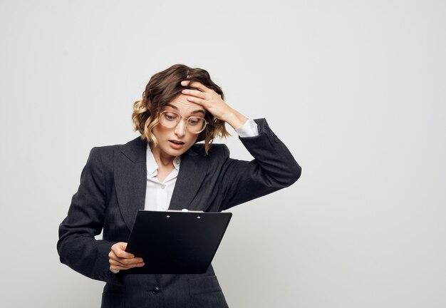 Een vrouw met documenten in een map op een lichte gebaren met haar handen