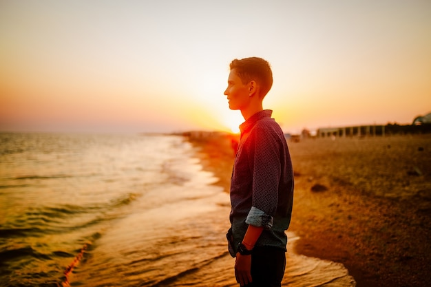 Een vrouw met een androgyne verschijning kijkt naar de zee bij zonsondergang