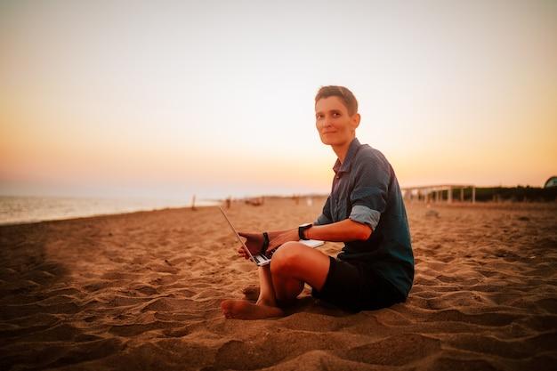 Een vrouw met een androgyne verschijning zit op een zandstrand