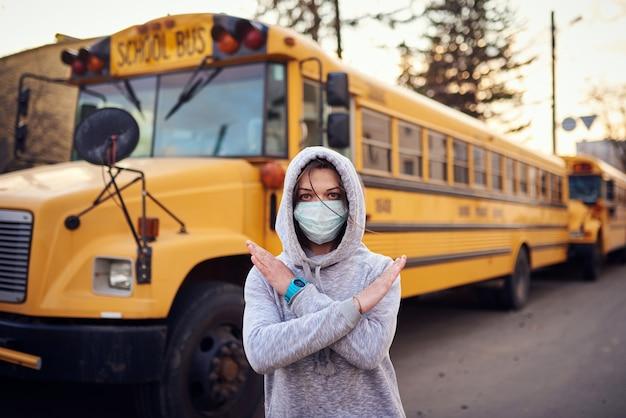 Een vrouw met een beschermend masker staat voor een schoolbus.