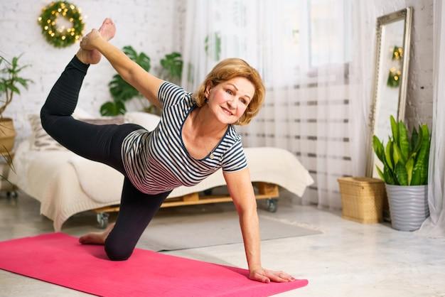 Een vrouw met een blanke uitstraling op volwassen leeftijd thuis in sportkleding doet aan sport