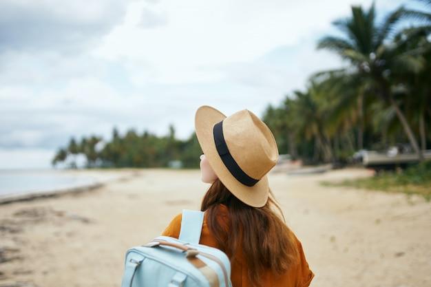 Een vrouw met een blauwe rugzak in een gele jurk en hoed loopt langs de oceaan langs het zand met palmbomen