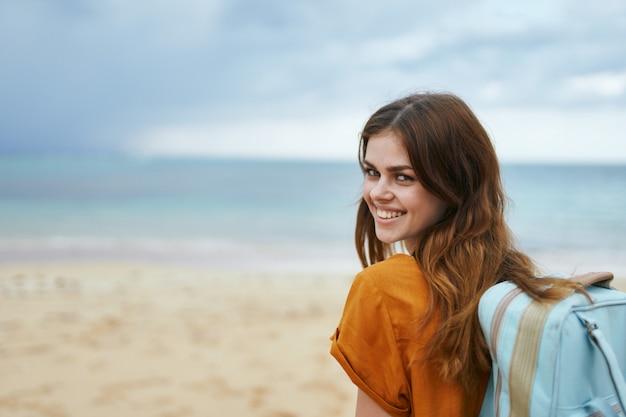 Een vrouw met een blauwe rugzak in een gele jurk loopt langs de oceaan langs het zand met palmbomen