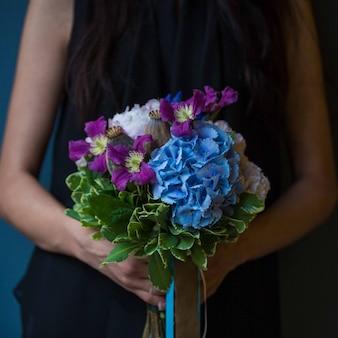 Een vrouw met een boeket paarse seringen en rozen in de hand