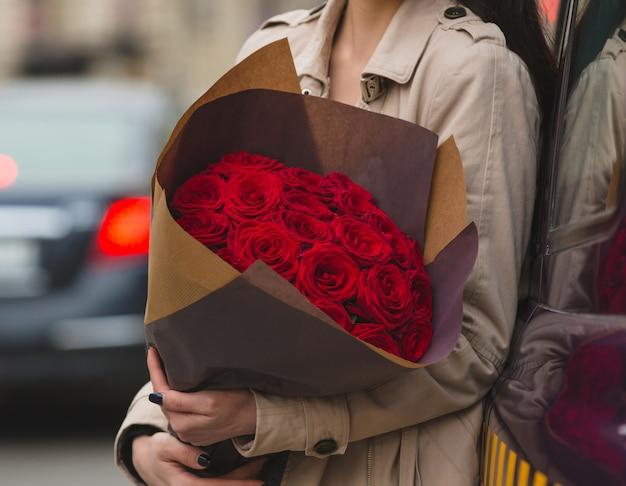 Een vrouw met een boeket rode fluwelen rozen in de hand