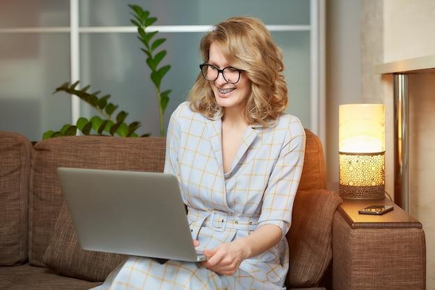 Een vrouw met een bril werkt op afstand op een laptop in haar appartement. een meisje dat lacht tijdens een videoconferentie met haar collega's thuis.