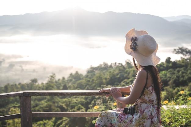 Een vrouw met een camera om het uitzicht op de bergen te bekijken