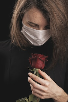 Een vrouw met een coronavirusmasker. mooie rode roos